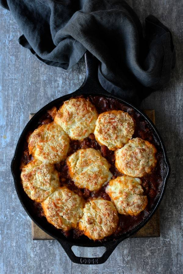 Skillet Turkey and Pinto Bean Chili with Pepper Jack Biscuit Topping Recipe | HeyFood — heyfoodapp.com