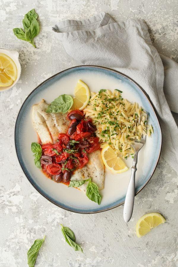 Baked Fish with Cherry Tomato Olive Sauce + Lemon Chive Asiago Orzo Recipe | HeyFood — heyfoodapp.com
